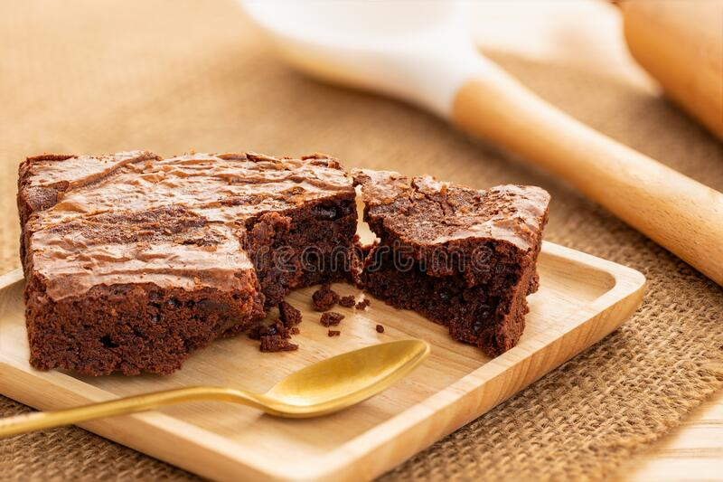 Brownies cake in a wooden plate with a golden spoon, large cooking spoon and rolling pin in the background on natural table mat. Brownies cake in a square wooden stock image