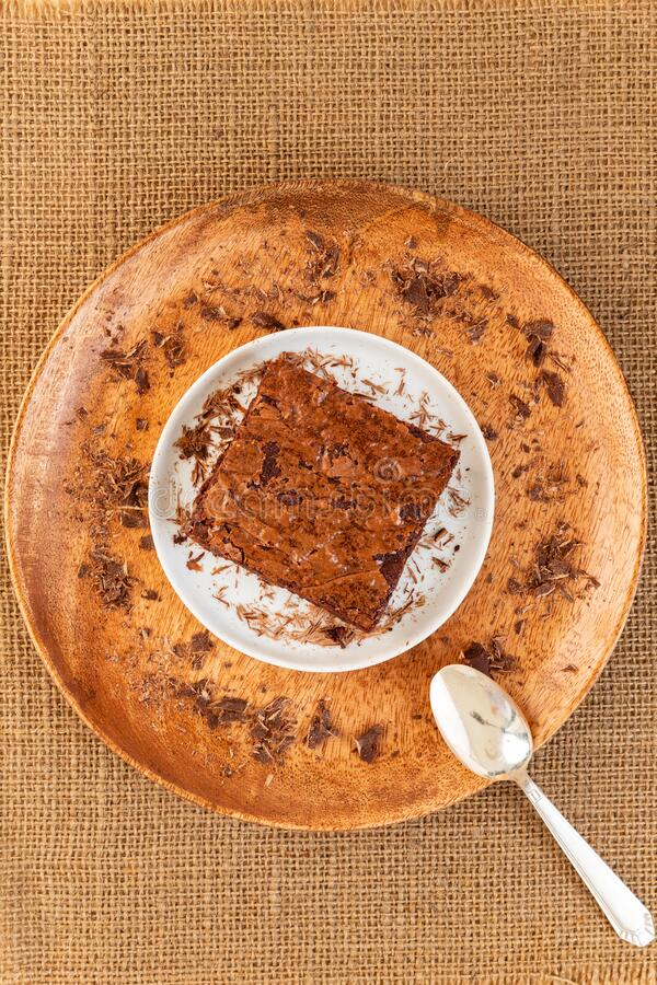 Brownies cake in a wooden plate with grated chocolate and spoon over a natural color string table mat background, Flat lay. Brownies cake in a wooden plate with stock images