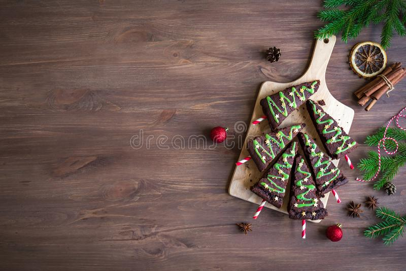 Brownies Christmas Trees. Chocolate Brownies in shape of Christmas Trees with green icing and festive sprinkles on wooden table, top view, copy space. Sweet royalty free stock photography