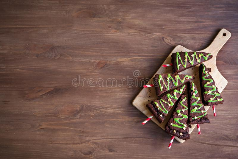 Brownies Christmas Trees. Chocolate Brownies in shape of Christmas Trees with green icing and festive sprinkles on wooden table, top view, copy space. Sweet stock photo