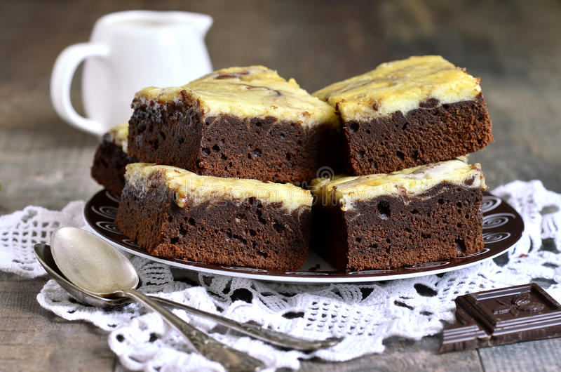 Brownies with curd. Chocolate brownies with curd or ricotta on a wooden table stock images