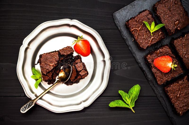 Brownies escuras caseiros do chocolate decoradas com morangos e folhas de hortelã sobre o fundo preto da ardósia, vista superior foto de stock royalty free