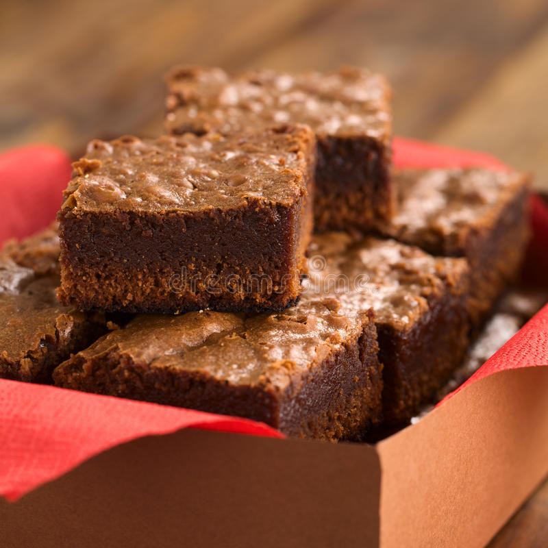 Brownies. Freshly baked brownies in a brown paper box with red napkin (Selective Focus, Focus on the first brownie on the top stock photos
