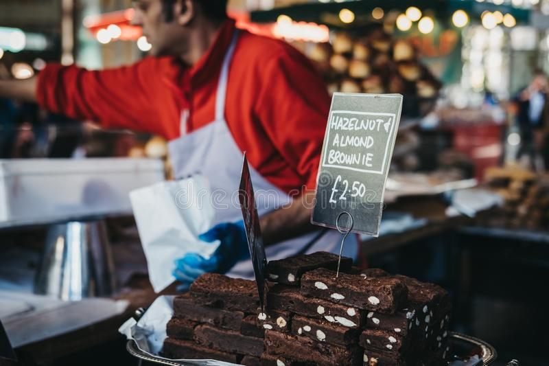 Brownies on sale at Borough Market, London, UK, seller on the background. Brownies on sale at Borough Market, seller on the background. Borough Market is one of stock photography