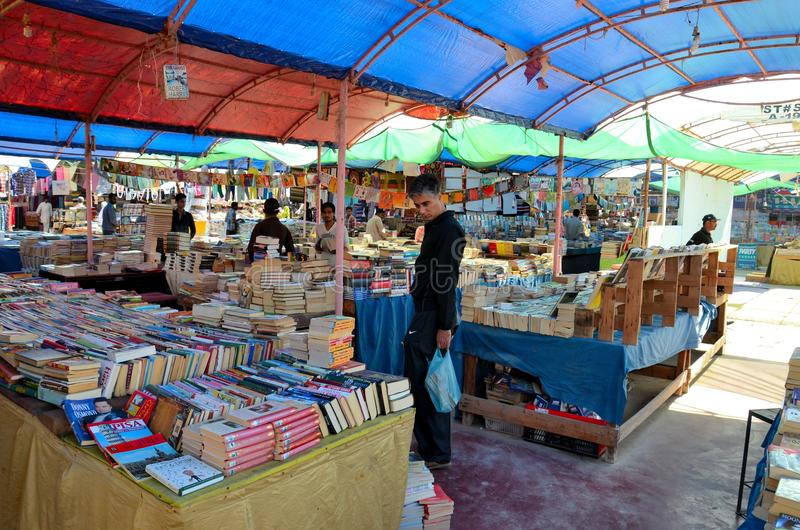 Browsing books at stall in bazaar Karachi Pakistan. Karachi, Pakistan - February 16, 2014: A man is seen browsing books resting on a table at a make-shift book royalty free stock photography