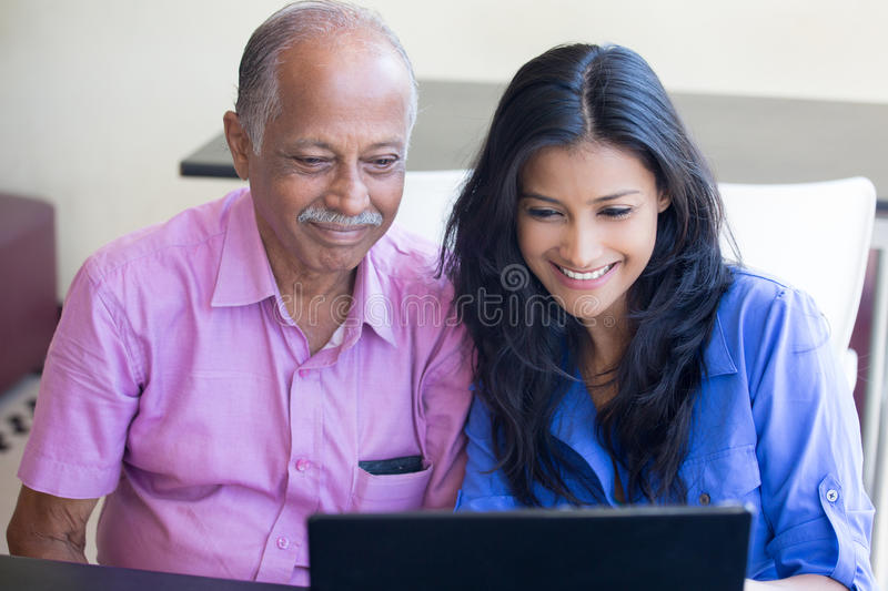 Browsing the internet. Closeup portrait, sitting young women showing elderly men to use black laptop, happy at what they see , indoors background stock photo