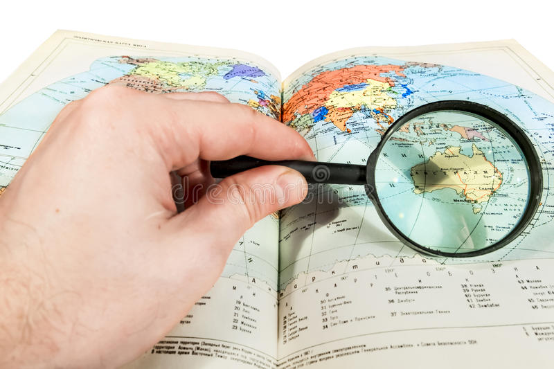 Browsing the map through a magnifying glass stock photography