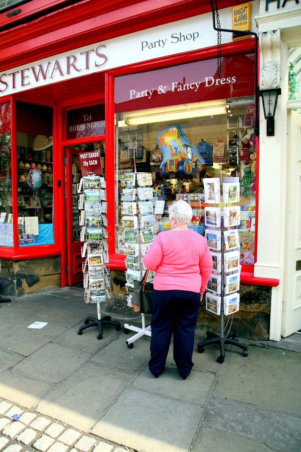 Browsing post cards. BAKEWELL, DERBYSHIRE, UK. APRIL 08, 2015. A senior lady browsing through a display of post cards outside a shop at Bakewell in Derbyshire stock photo