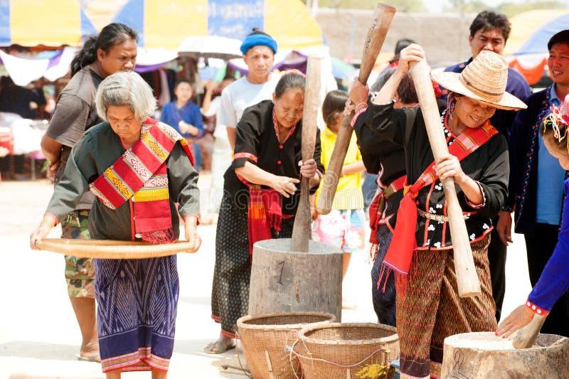 Broyage de femme de minorité de PhuThai et riz de vannage images stock