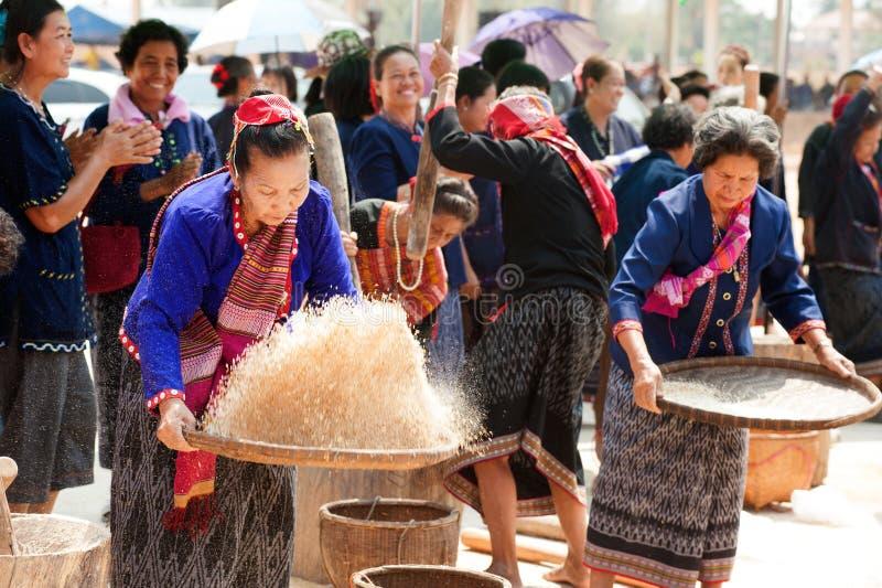 Broyage thaïlandais de femme de minorité de Phu et riz de vannage images libres de droits