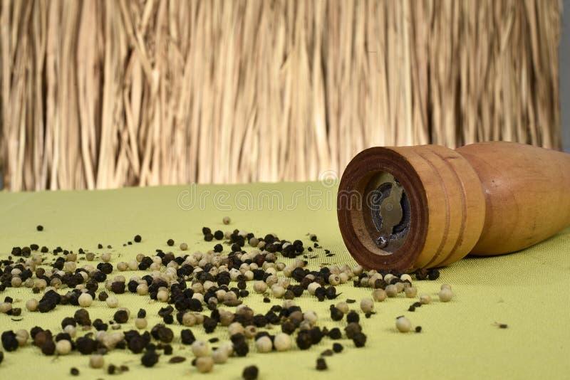 Broyeur de poivre avec des grains de poivrons sans fond de paille images libres de droits