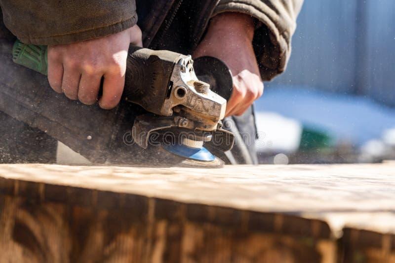 Broyeur extérieure en bois de meulage de fond avec la meule abrasive le charpentier de travailleur rectifie le bois enlevant de v photos stock