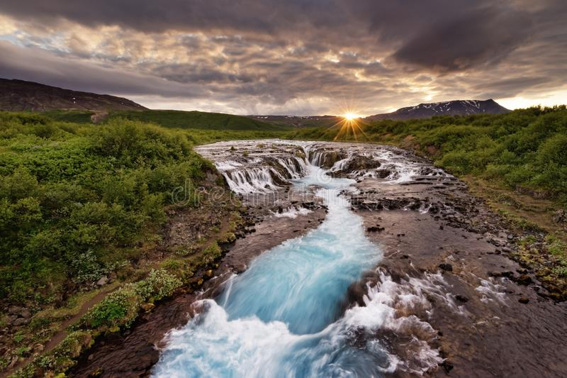 Bruarfoss - Large waterfall in the evening light. Large waterfall in a wide landscape with evening light, sunset with rays on a mountain range, water movement in stock images