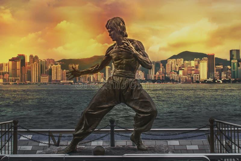 Bruce Lee staty på avenyn av stjärnor Horisont över Victoria Harbour i bakgrunden på solnedgången royaltyfria bilder