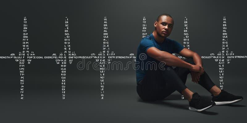 bruch Hübscher Sportler, der über dunklem Hintergrund sitzt Grafikdiagramm stockfotos