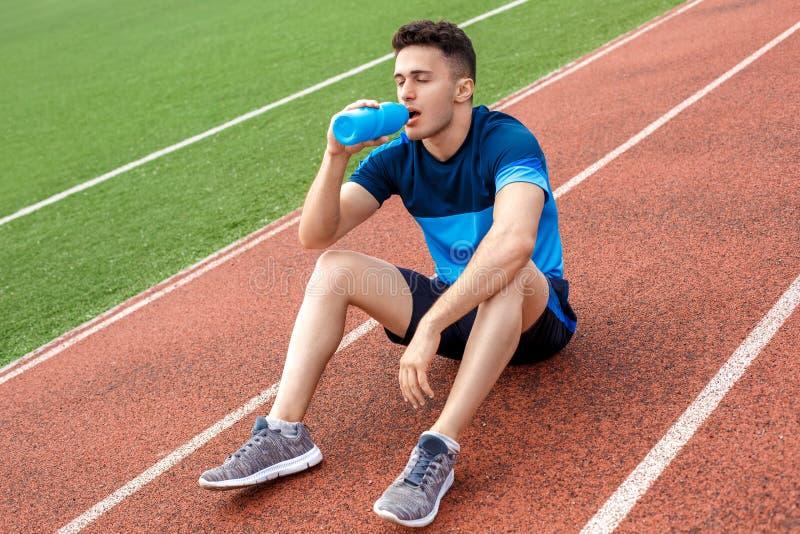 Bruch haben Junger Mann auf Stadion außerhalb der sitzenden durstigen geschlossenen Augen des Trinkwassers stockbilder