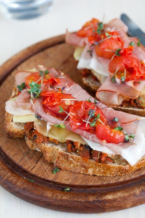 Bruchetta delicioso con el jamón y el tomate imagenes de archivo