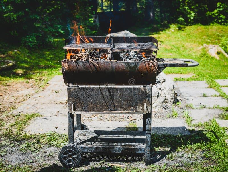 Bruciando e preriscaldando il vecchio barbecue arrugginito grigli il g sporco di pulizia fotografia stock libera da diritti