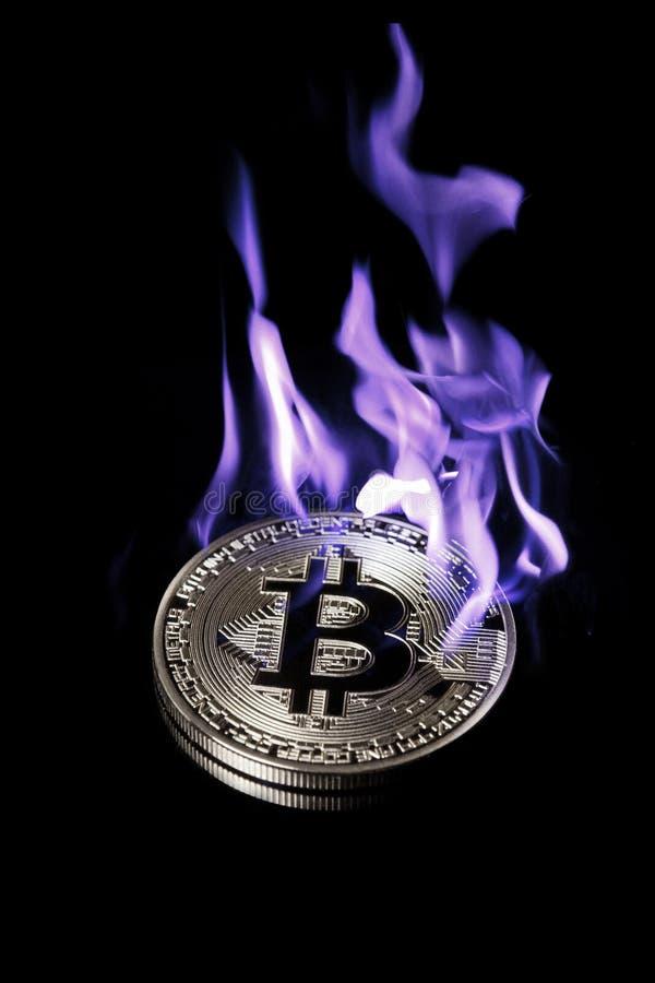Bruciando nel bitcoin blu dell'argento del fuoco isolato sul nero fotografie stock libere da diritti
