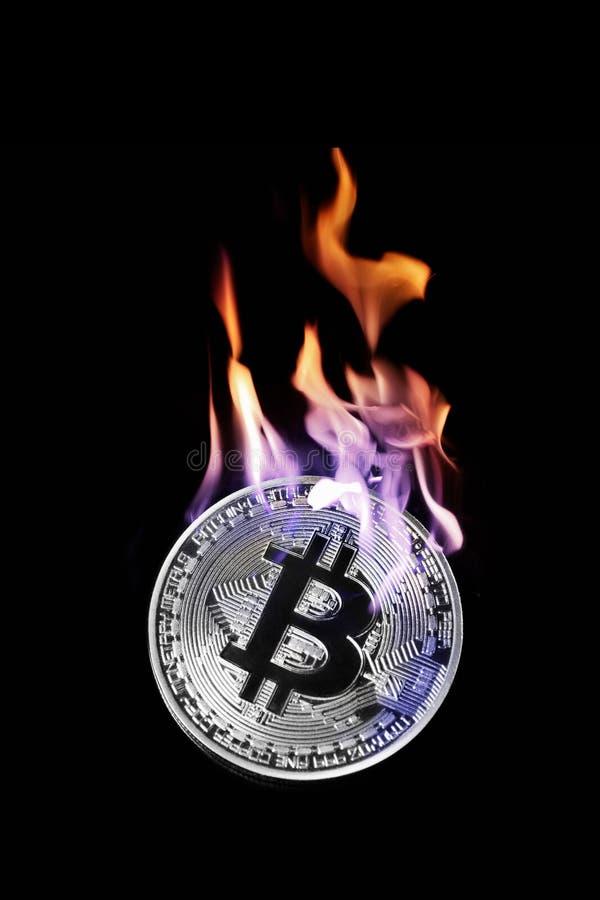 Bruciando nel bitcoin dell'argento del fuoco isolato sul nero fotografie stock