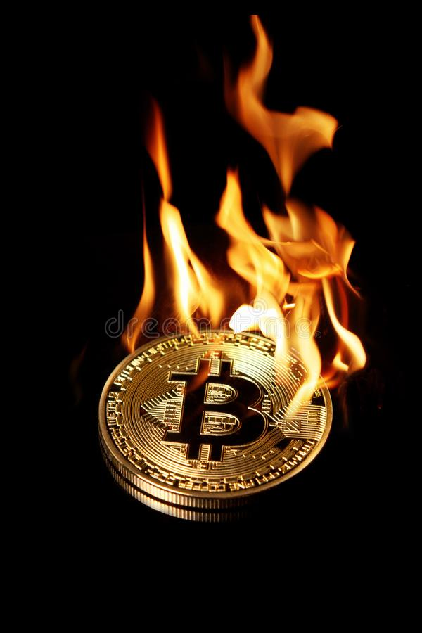 Bruciando nel bitcoin dorato del fuoco isolato sul nero fotografie stock