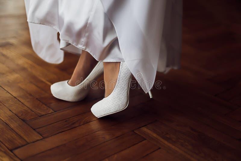 Brud- bröllopskor Härliga vita skor på höga häl Kvinnaben royaltyfria foton