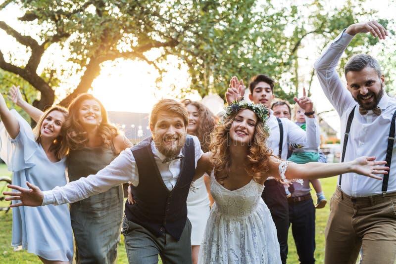 Brud brudgum, gäster som poserar för fotoet på bröllopmottagandet utanför i trädgården arkivbild