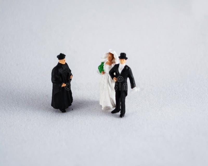 Brud, brudgum och präst på vit arkivfoton