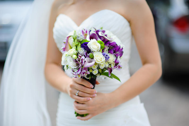 Brud- bukett av purpurfärgade och vita blommor i händer av bruden royaltyfria foton
