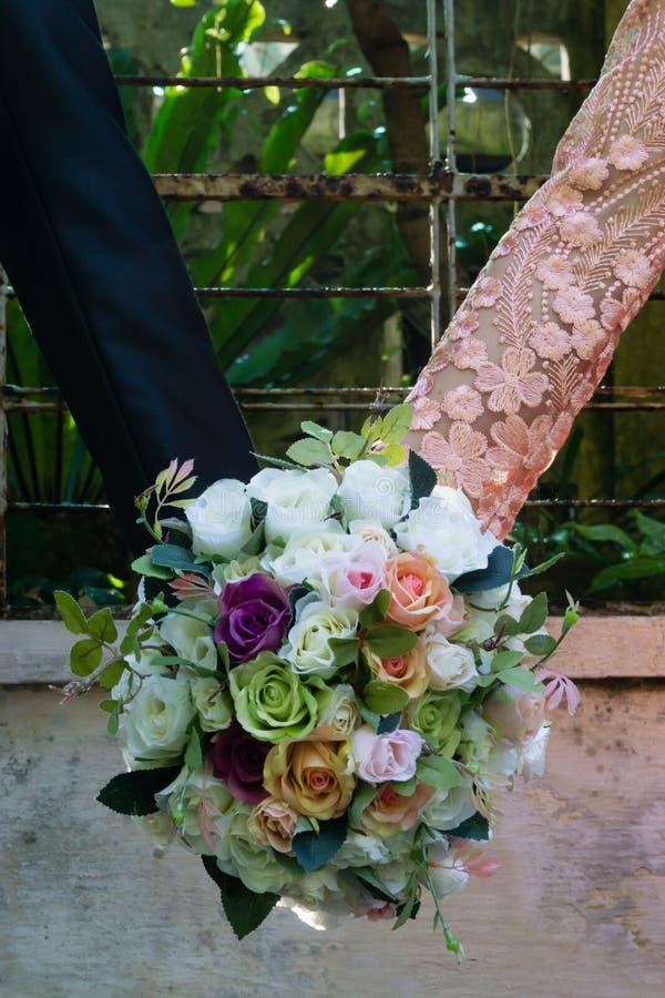 Brud- bukett av rosor som rymmer vid bruden och brudgummen fotografering för bildbyråer