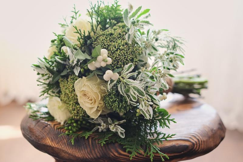 Brud- bukett av vita och gröna blommaställningar på en stol mot ett ljust tyg royaltyfria foton