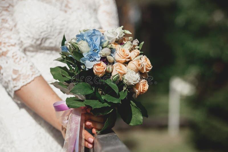 Brud- bukett för brudinnehav med vita och krämiga rosor och blåa blommor utomhus arkivfoto