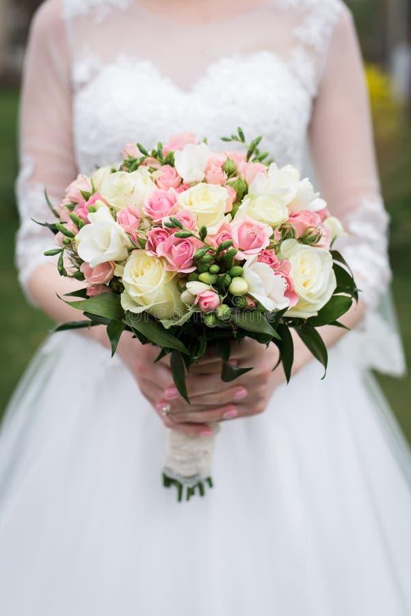 Brud- bukett med vita och rosa rosor Bruden i den vita bröllopsklänningen rymmer en bröllopbukett med vit och rosa färgro royaltyfri bild