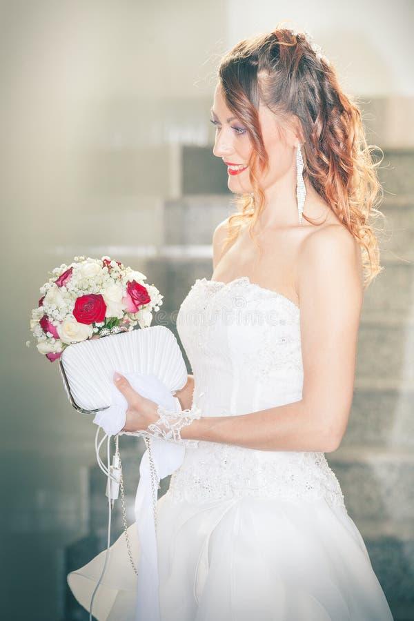 Brud, bukett och handväska Bröllopkappa inre fotografering för bildbyråer
