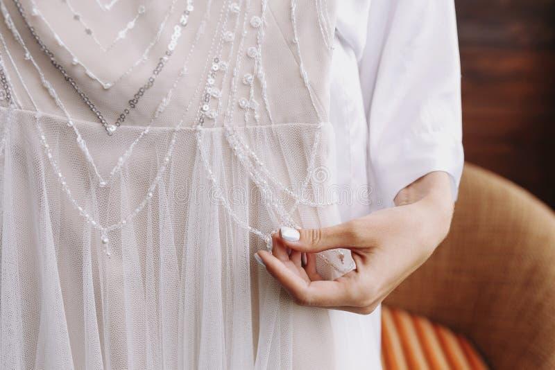 Brud förberedelser bröllop manicure Brudhandlagpärlor på din vita bröllopsklänning vid handen med pärlan spikar arkivbilder