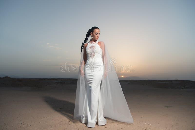 Brud i bröllopkappa på solnedgånghimmel Kvinna i den vita klänningen i öken Sinnlig kvinna med brunetthår Modemodell i sanddyn royaltyfri foto
