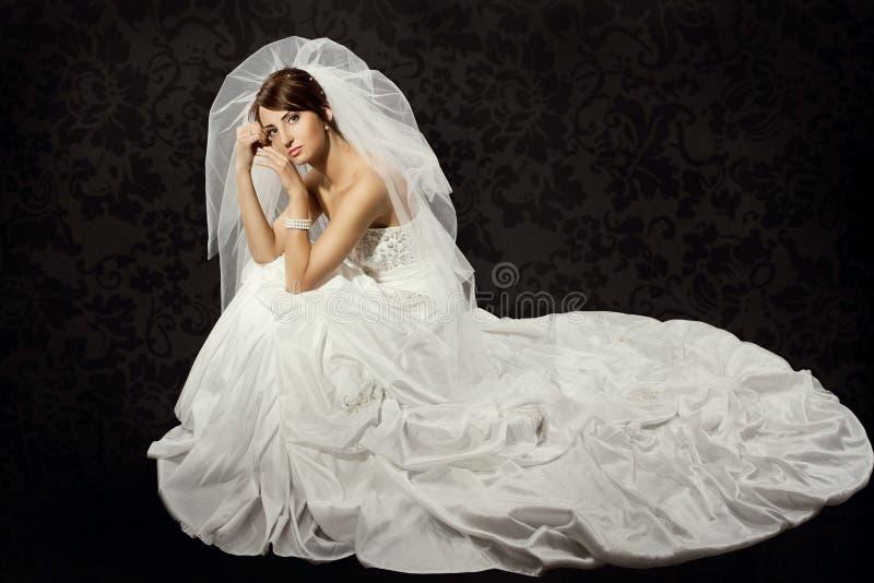 Brud i bröllopsklänning över mörk bakgrund arkivfoto