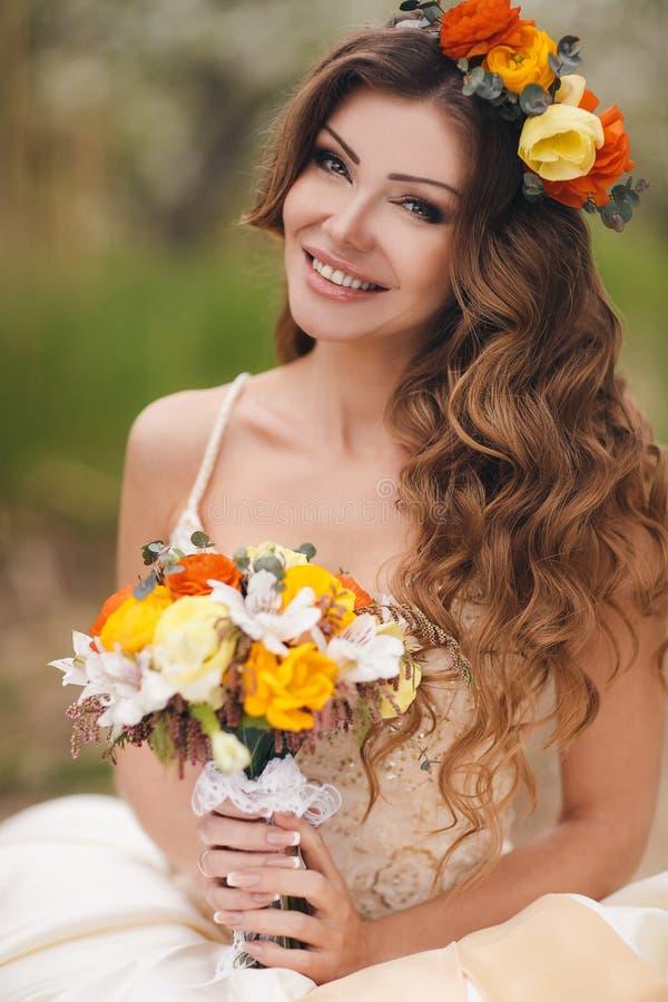 Brud i bröllopsklänning i parkera på våren royaltyfri foto