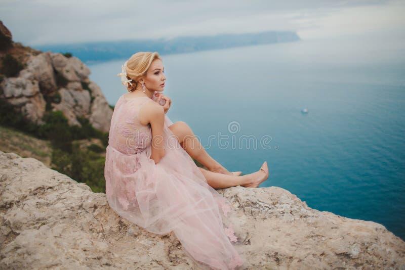 Brud i bröllopsklänninganseende på en vagga arkivfoton