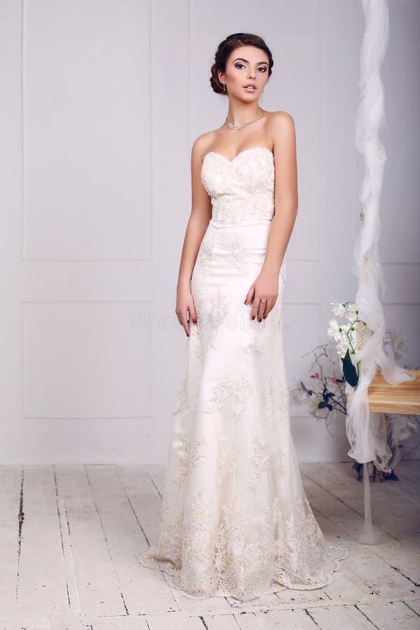 Brud i bröllopsklänningen som poserar bredvid en dekorerad gunga arkivfoton