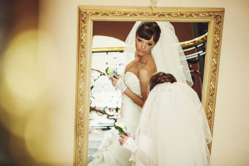 Brud i den vita klänninginnehavblomman och se miroren fotografering för bildbyråer