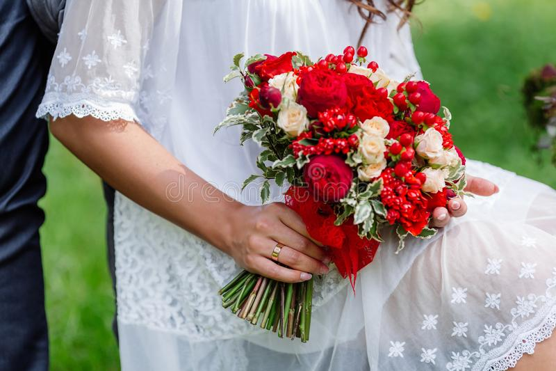 Brud i det vita klänninginnehavet i delikata händer, dyr moderiktig brud- bröllopbukett av blommor i marsala och röda färger clo arkivbild