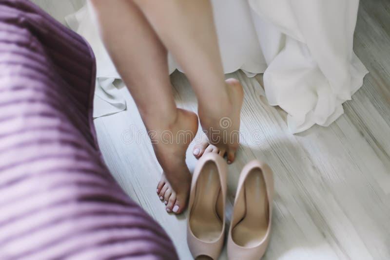 Brud i elegant klassisk bröllopsklänning med skor Morgon av bruden royaltyfri bild