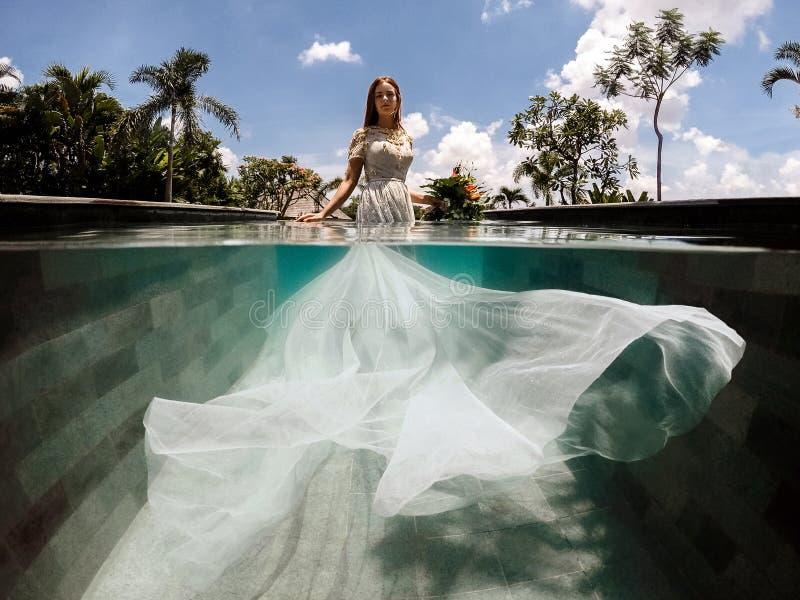 Brud i en bröllopsklänning i en simbassäng royaltyfria bilder