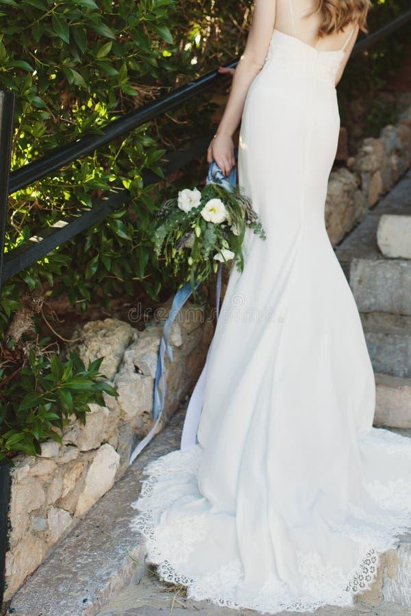 Brud i en hållande bukett för härlig lång vit bröllopsklänning av blommor royaltyfri bild