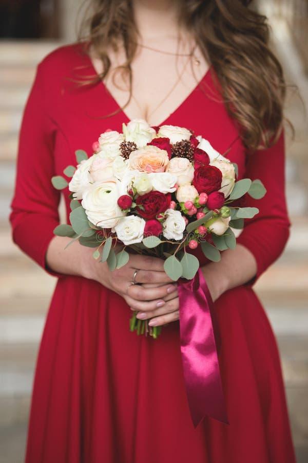 Brud i en röd klänning Brudtärna i en röd klänning Bröllopbukett med ett rött band royaltyfri fotografi