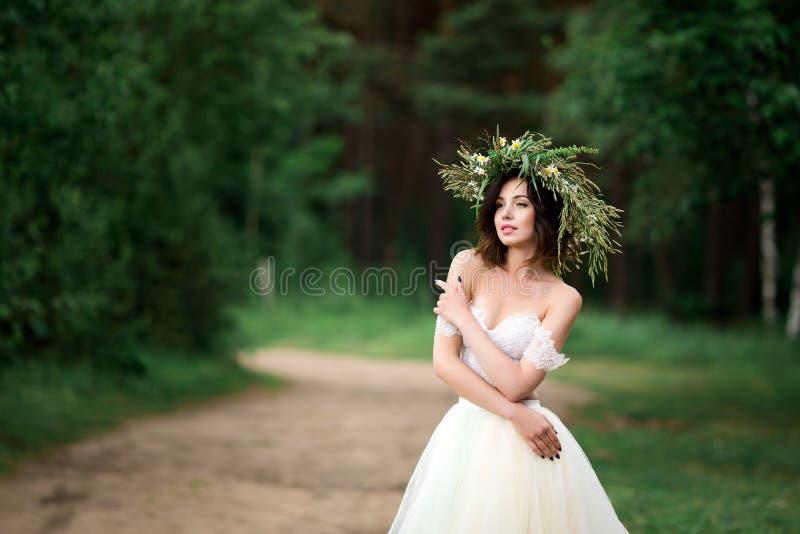 Brud i en vit klänning med en krans av blommor royaltyfria foton