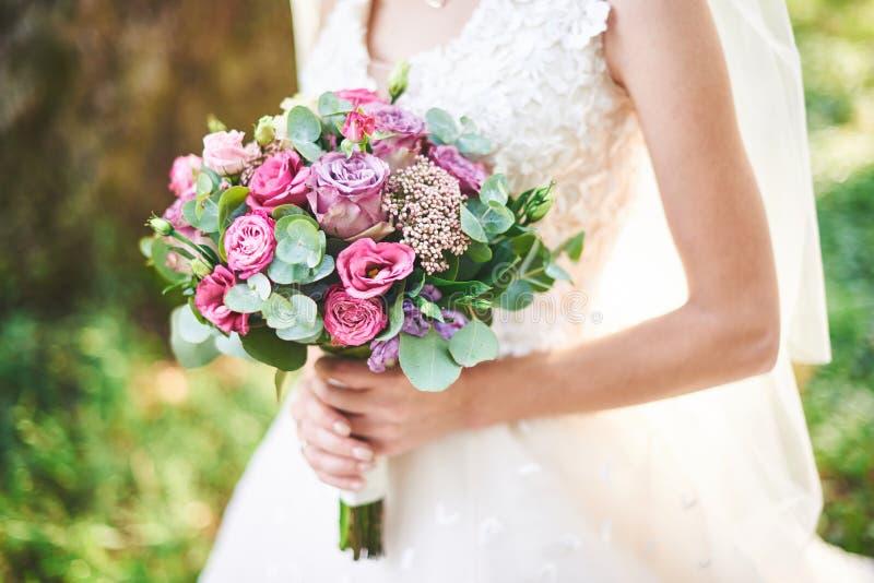 Brud i en vit klänning som rymmer en bukett av lilablommor och grönska på bakgrunden av grönt gräs arkivfoton