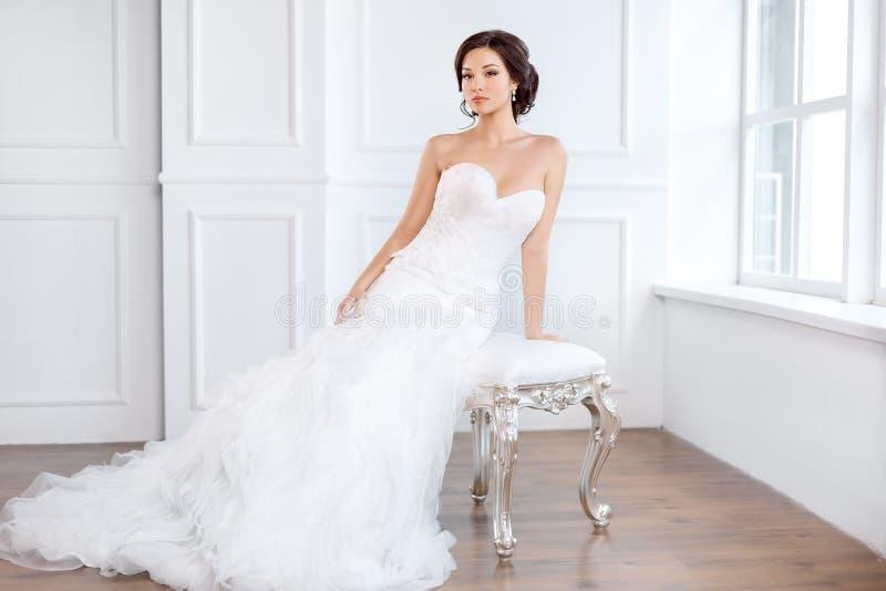 Brud i härligt klänningsammanträde på stol inomhus royaltyfria foton