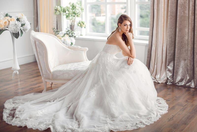Brud i härligt klänningsammanträde som inomhus vilar på soffan royaltyfri fotografi
